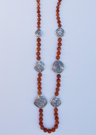 Detail of an apple coral rounds necklace with 925 silver crabs cast by Old World craftsmen in the Czech Republic