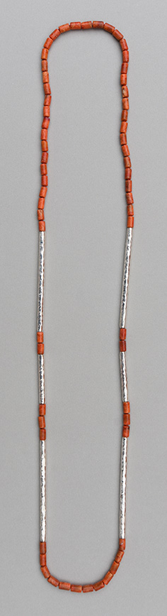 A necklace with six paired hammered 925 silver tubes in different lengths combined with apple coral tubes