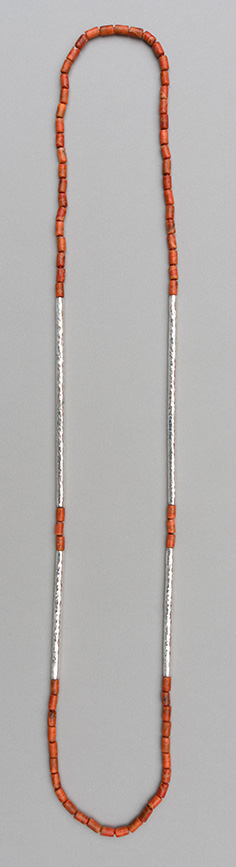 A necklace with two pairs of hammered 925 silver tubes of different length combined with apple coral tubes