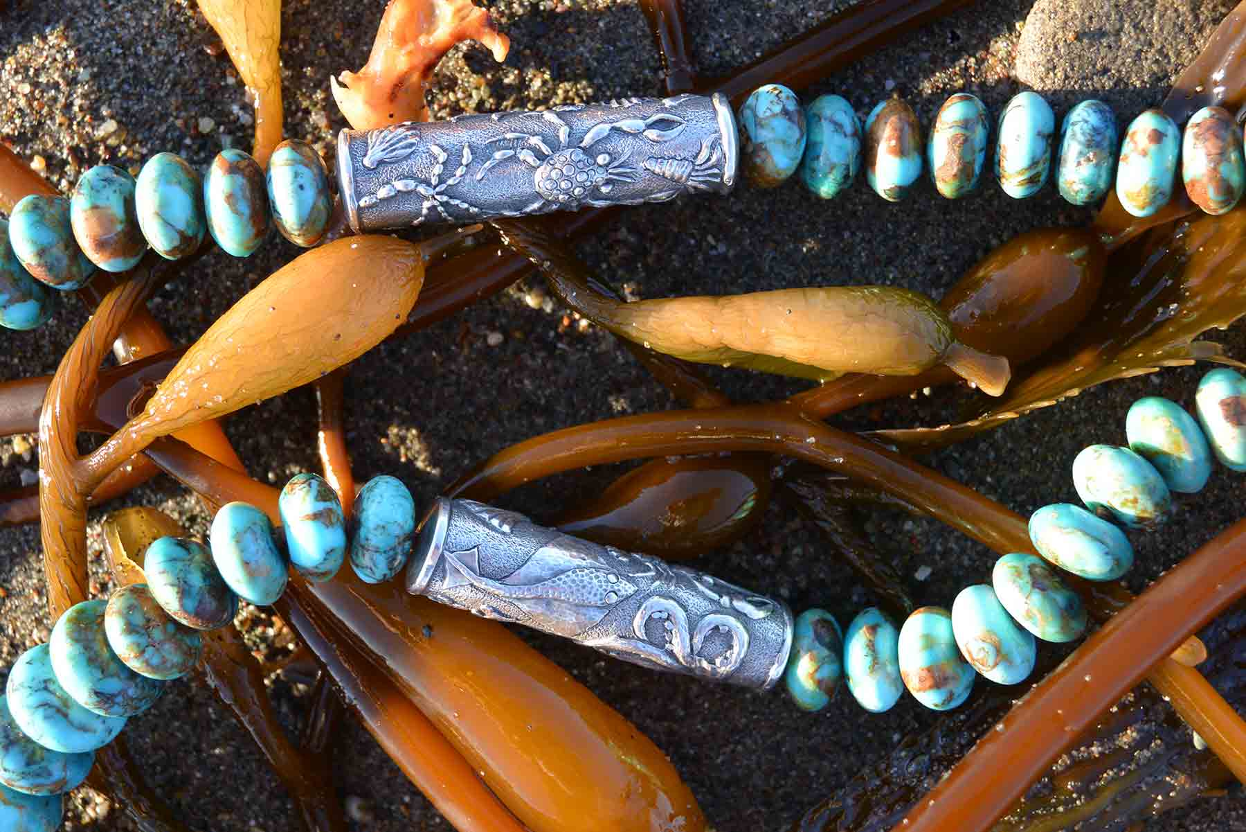 Giant perennial kelp sets off a necklace of Arizona Boulder turquoise rondelles and Old World cast 925 silver cylinders bearing motifs of the Sea Creatures Collection, by Kamila Kubelik.