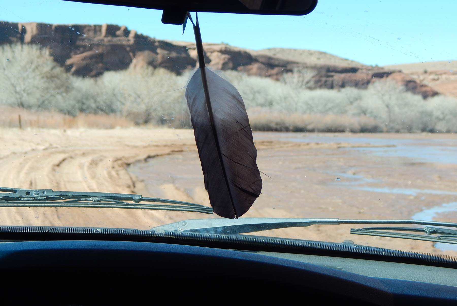 A feather, here hanging from the rear-view mirror of an off-road truck traversing Canyon de Chelly near Chindle in the Navajo Nation, is one of the inspirations for the Southwest Collection of Arizona turquoise, coral and Old World cast 925 silver jewelry by Kamila Kubelik.