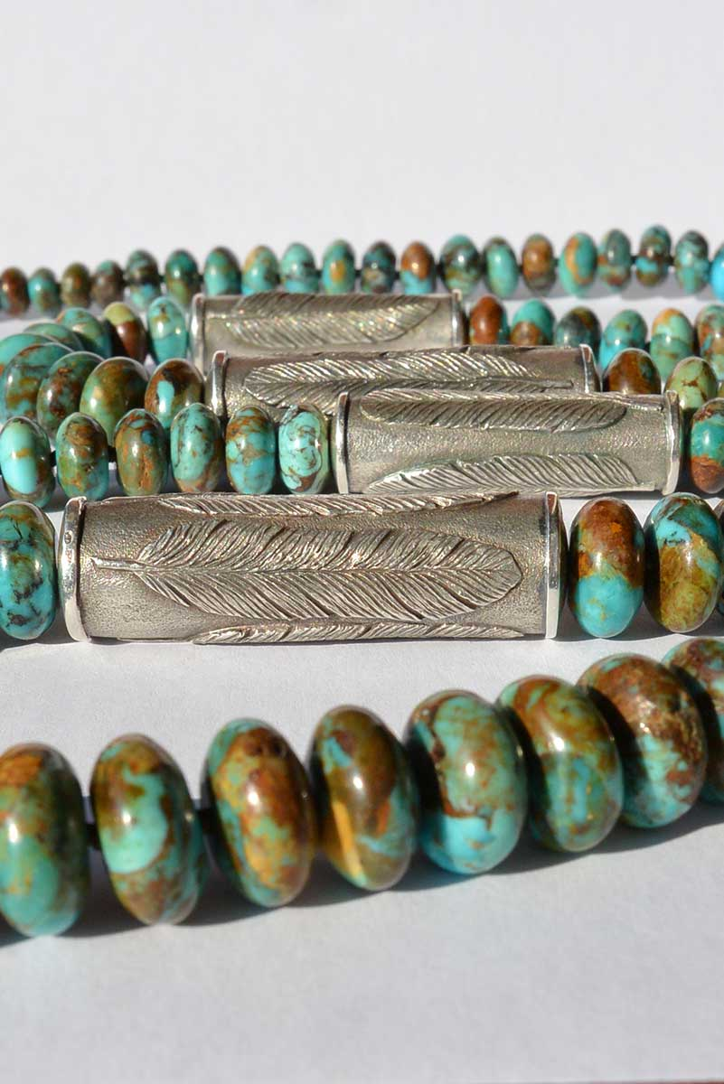 Detail of a necklace with Arizona Boulder turquoise rondelles and Old World cast 925 silver cylinders bearing a feather motif, from the Southwest Collection of jewelry by Kamila Kubelik.