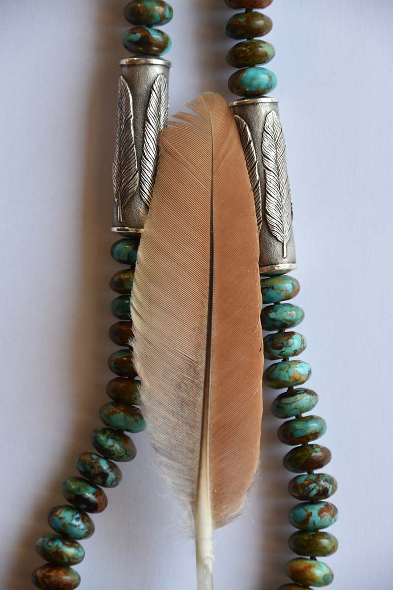 An inspirational kestrel feather creatively incorporated into an Old World cast 925 silver cylinder and combined with Arizona Boulder turquoise rondelles as part of a piece of jewelry from the Southwest collection by designer Kamila Kubelik.